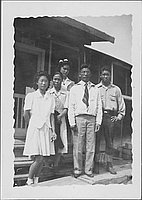 [Three women and two men standing on barracks porch steps, Rohwer, Arkansas]