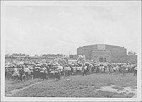 [Funeral gathering outside of large building with American flag, Rohwer, Arkansas, September 30, 1944.