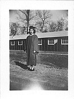 [Young woman in graduation gown and high heels in front of barracks, Rohwer, Arkansas, June 7, 1945]