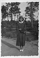 [Young woman in eyeglasses and graduation gown holding diploma, Rohwer, Arkansas, 1942-1945]