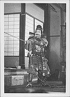[Warrior with fan in mouth and holding rope in Kabuki play, Rohwer, Arkansas]