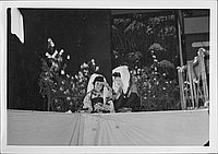 [Blind musican and companion sitting in front of flowers in Kabuki play, Rohwer, Arakansas, Novermber 12, 1944]