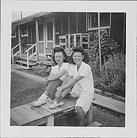 [Two young women sitting on wooden platform in front of barracks, 1-4-A and 1-4-B, Rohwer, Arkansas, October 1, 1944]