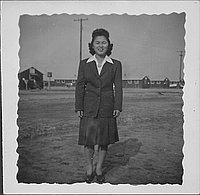 [Young woman in suit standing in open area, full-length portrait, Rohwer, Arkansas]