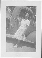 [Young woman with flower in her hair holding onto door handle of truck, Rohwer, Arkansas]