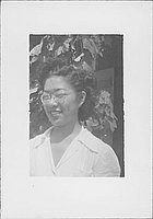 [Woman in eyeglasses in front of vines, head and shoulder portrait, Rohwer, Arkansas]
