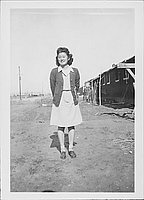[Young woman wearing letterman sweater, full-length portrait, Rohwer, Arkansas, January 29, 1944 or 1945]