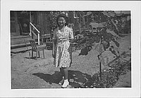 [[Young woman in floral dress next to leafy plant, Rohwer, Arkansas]