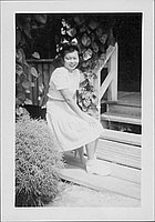 [Young woman sitting in front of porch, Rohwer, Arkansas, October 31, 1944]