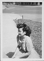 [Young woman in polka dot dress kneeling on sidewalk, Rohwer, Arkansas]