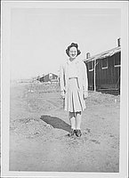 [Sakaye Nakatsuru in sweater and pleated skirt in open area near barracks, Rohwer, Arkansas, January 1944/5?]