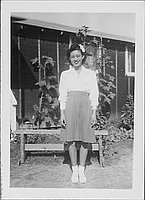 [Young woman in eyeglasses with a flower in hair in front of barracks, Rohwer, Arkansas, October 15, 1944]
