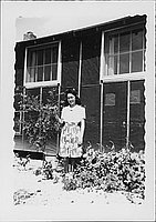 [Young woman standing next to tree in front of barracks, Rohwer, Arkansas]