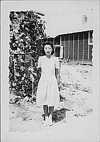 [Woman in spiral patterned dress in front of vines and barracks, full-length portrait, Rohwer, Arkansas, July 9, 1944]