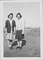 [Sisters Misako and Sakaye Nakatsuru standing side-by-side in open area, Rohwer, Arkansas, January 29, 1945]