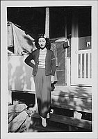 [Young woman in trousers and flower in hair on barracks porch steps, Rohwer, Arkansas, October 16, 1944]