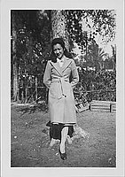 [Young woman in trenchcoat in front of tree, full-length portrait, Rohwer, Arkansas, October 16, 1944]