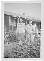 [Two older women standing on path between gardens, Rohwer, Arkansas, October 1944]