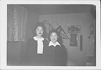 [Two young women standing in room in front of pennants and pictures, Rohwer, Arkansas, January 22, 1945]