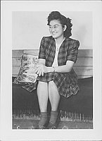 [Young woman in plaid suit sitting on bench, Rohwer, Arkansas, April 29, 1945]
