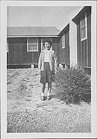 [Young woman standing next to shrub and barracks, Rohwer, Arkansas]