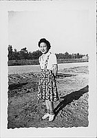 [Young woman in patterned jumper standing in an empty lot, Rohwer, Arkansas]