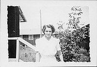 [Caucasian woman outdoors next to barracks railing, half-portrait, Rohwer, Arkansas, July 29, 1944]