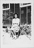 [Young woman sitting on folding chair in front of barracks, Rohwer, Arkansas, August 3, 1944]