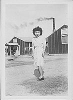 [Young woman in front of mess hall with smoking chimney, full-length portrait, Rohwer, Arkansas, February 28, 1945]