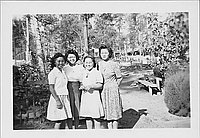 [Four young women standing on wooded path, Rohwer, Arkansas, October 28, 1944]
