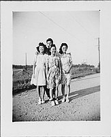 [Three young men and a young man standing unpaved road, Rohwer, Arkansas, October 28, 1944]