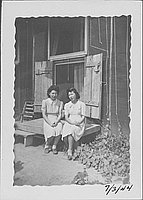 [Two women sitting on deck in front of barracks double-doors, Rohwer, Arkansas, July 3, 1944]