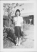 [Young woman standing on path next to tree and shrubs, Rohwer, Arkansas]