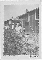 [Woman standing behind shrubs near clothesline, Rohwer, Arkansas, July 3, 1944]