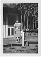 [Woman in patterned dress standing on barracks porch steps next to hechima gourds, Rohwer, Arkansas]
