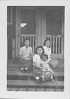 [Three women and little girl sitting on barracks porch steps, Rohwer, Arkansas, April 15, 1945]