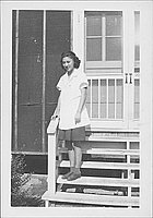 [Young woman in white smock standing on steps, full-length portrait, Rohwer, Arkansas]