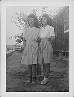 [Two young women standing side-by-side in front of small tree and barracks, full-length portrait, Rohwer, Arkansas]