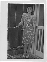 [Young woman in floral patterned suit standing on barracks porch, full-length portrait, Rohwer, Arkansas]