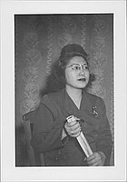 [Woman in eyeglasses and suit holding rolled papers, half-portrait Rohwer, Arkansas, April 12, 1945]