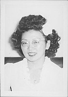 [Woman in eyeglasses and a white flower in hair, head and shoulder portrait, Rohwer, Arkansas, October 29, 1944]