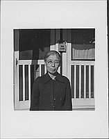 [Older woman with eyeglasses in front of barracks, half-portrait, Rohwer, Arkansas]