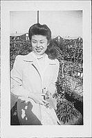 [Woman in white coat holding an envelope in garden, three-quarter portrait, Rohwer, Arkansas, November 25, 1944]