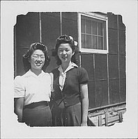 [Two women standing in front of barracks wall, half-portrait, Rohwer, Arkansas]