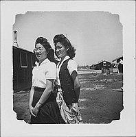 [Two women standing in open area between barracks, three-quarter portrait, Rohwer, Arkansas]