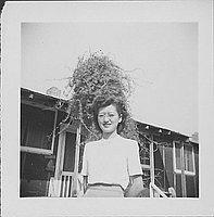 [Woman wearing eyeglasses in front of barracks porch with vine, Rohwer, Arkansas, September 23, 1944]