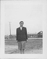 [Woman in dark jacket and plaid skirt, three-quarter portrait, Rohwer, Arkansas]