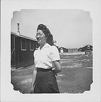 [Woman with dimples and eyeglasses standing in open area between barracks, three-quarter portrait, Rohwer, Arkansas]