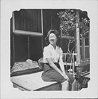 [Woman wearing eyeglasses sitting on wooden bin, Rohwer, Arkansas]