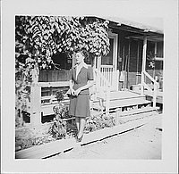 [Woman in suit and eyeglasses posed in front of barracks, 2-7-B, full-length portrait, Rohwer, Arkansas]
